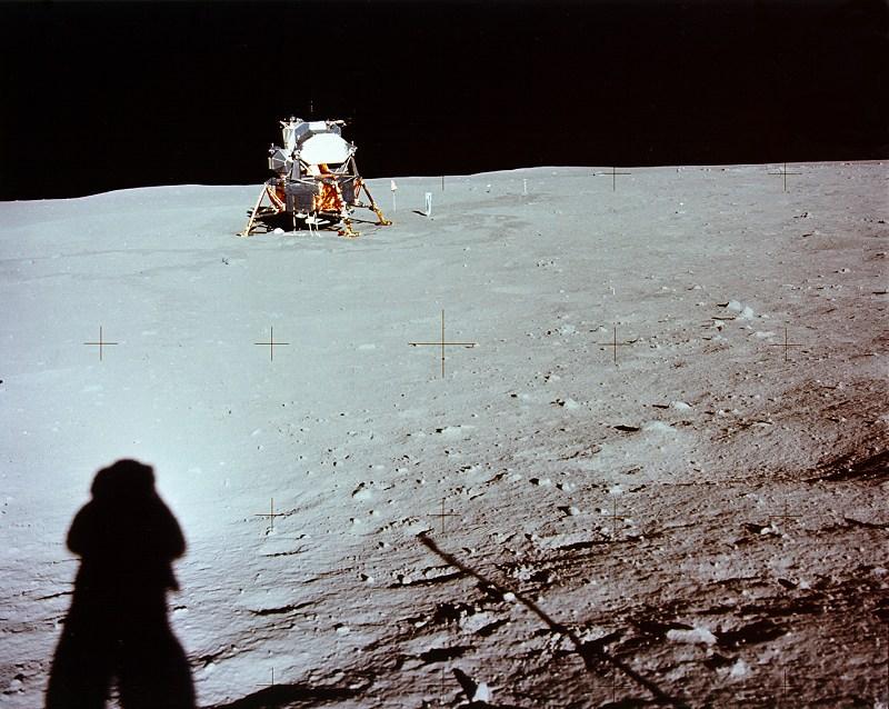Lądownik Księżycowy (fot. NASA) - fotografia wykonana przez N. Amstronga. Na pierwszym planie widoczny jego cień, przy lądowniku amerykańska flaga i przyrząd do badań wiatru słonecznego.